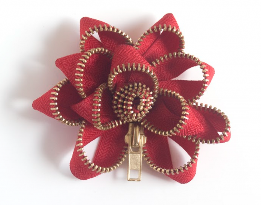 A red and gold flower made of a zipper