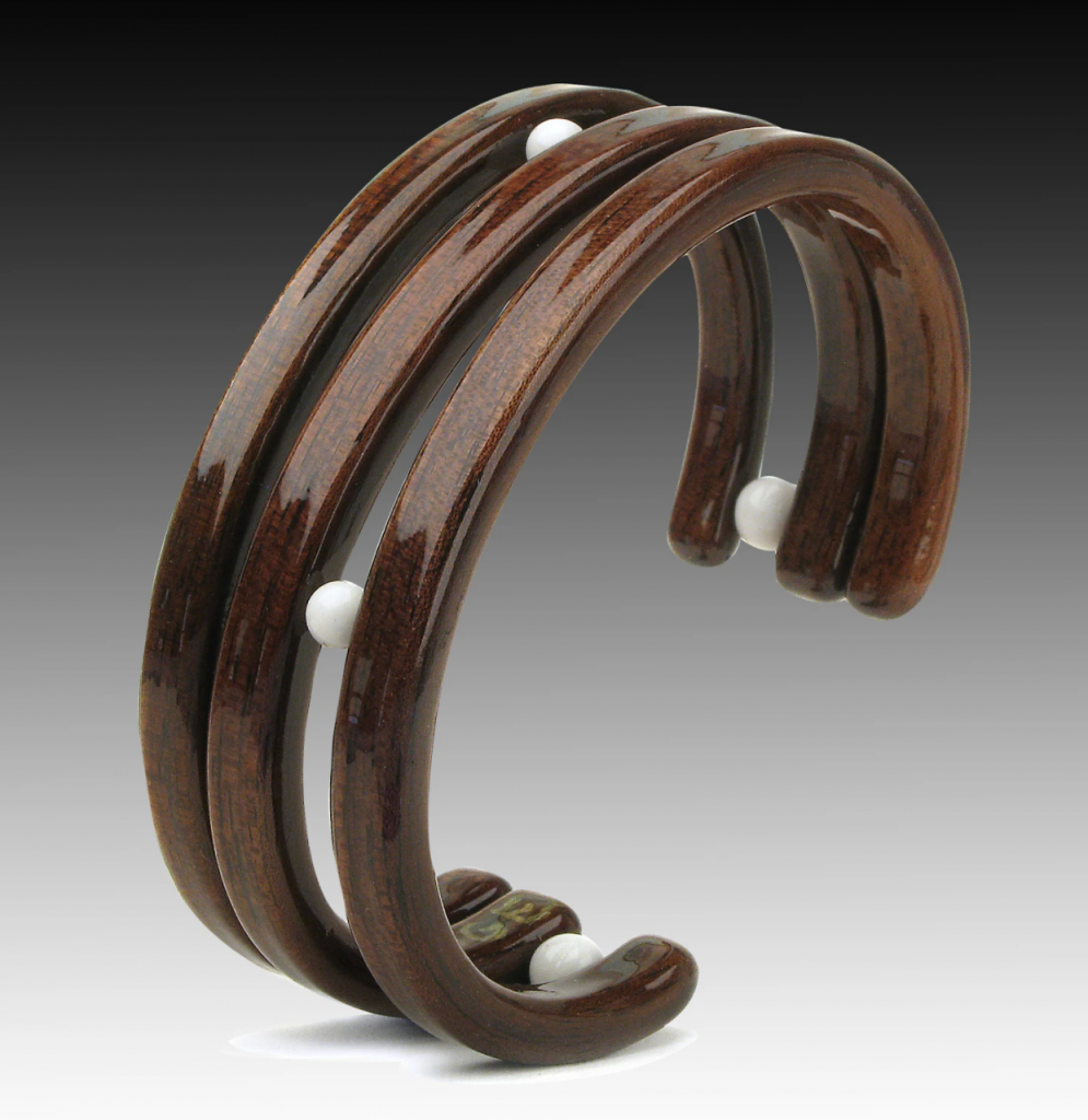 a three tiered wooden bangle with pearls set between.