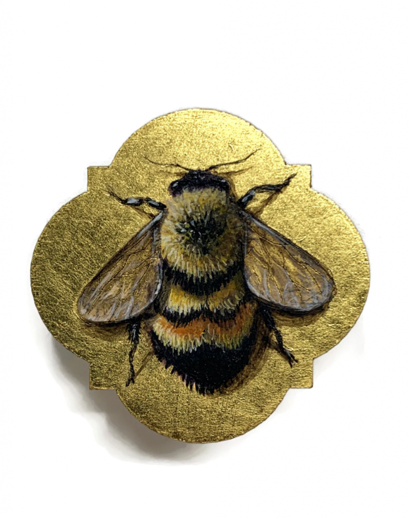 A small brooch painted with a bee and gilded with gold
